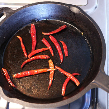 Frying dried chiles.